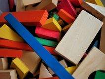 Kids Wooden Building Blocks Brightly Colored in Toy Box. A jumble of colorful wooden building blocks in a children`s toy collection royalty free stock images