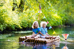 Kids on wooden raft Stock Photography