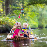 Kids on wooden raft. Two children on wooden raft catching fish with a colorful net in a river and playing with water on hot summer day. Outdoor fun and adventure Stock Photos