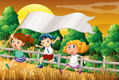 Kids at the woods holding an empty banner Royalty Free Stock Image