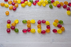 Kids word made from candies. On white wooden background Stock Photos