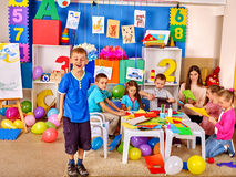 Kids working with colored paper on table in kindergarten . Stock Photo