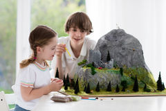 Kids working on model building project for school. Children work on model building school project. Kids build miniature scale model mountain for geography class Stock Photography