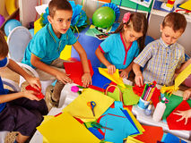 Kids working with paper on table in kindergarten . Royalty Free Stock Image