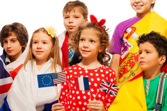 Kids wrapped in flags of USA and European nations Stock Photo
