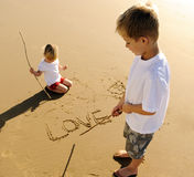 Kids writing in sand Stock Photography
