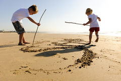 Kids writing in sand. Lovely young brother and sister write words in the sand together Stock Images