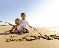 Kids writing in sand Royalty Free Stock Images