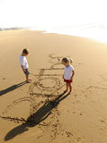 Kids writing in sand Stock Photos