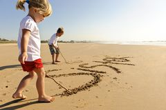 Kids writing in sand Stock Images
