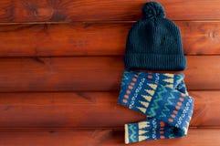 Kids& x27;有一条五颜六色的围巾的深蓝帽子在木蟒蛇放置 库存照片