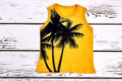 Kids yellow printed t-shirt. Childrens sleeveless t-shirt with a pattern of palm trree on white wooden ackground. Childs summer outfit royalty free stock image