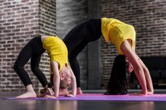 Free Kids Yoga Female Teacher Training A Child Girl Standing In Wheel Pose Working Out In Stylish Sports Studio Royalty Free Stock Photos - 111909838