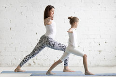 Kids yoga teacher training with a little girl Virabhadrasana pos. Kids yoga female teacher training a little child, practicing yoga, standing in Warrior one Stock Images