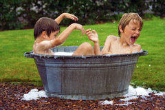 Kids in zinc bathtub. Kids having fun, splashing in zinc bathtub Stock Photos