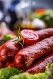 kiełbasa Chorizo kiełbasa Surowa uwędzona kiełbasa z jarzynową dekoracją Sałata czosnku sałatkowy zielarski rozmarynowy pomidorow fotografia royalty free