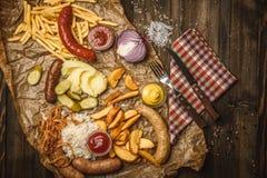 Kiełbasy na grill niecce drewniany tło Zdjęcia Stock