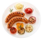 Kiełbasy piec na grillu z warzywami i kumberlandem na talerzu isolate obrazy royalty free