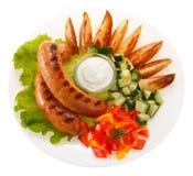 Kiełbasy piec na grillu z warzywami i kumberlandem na talerzu isolate zdjęcie stock