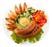Kiełbasy piec na grillu z warzywami i kumberlandem na talerzu isolate obrazy stock
