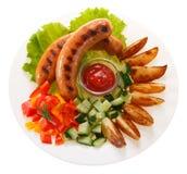 Kiełbasy piec na grillu z warzywami i kumberlandem na talerzu isolate zdjęcie royalty free