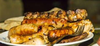 Kiełbasiane wieprzowina ziobro kurczaka nogi na grilla grillu na talerzu Zdjęcia Stock