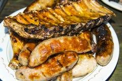 Kiełbasiane wieprzowina ziobro kurczaka nogi na grilla grillu na talerzu Obrazy Stock