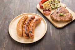 Kiełbasy i piec na grillu wieprzowina kotlecik na drewnianym tle Fotografia Stock