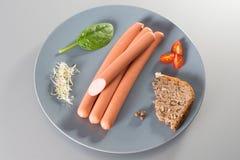 Kiełbasy z chlebem na popielatym talerzu na srebnym tle Obrazy Stock