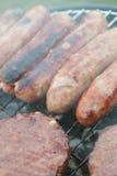 Kiełbasy i hamburgery na grillu Zdjęcia Stock