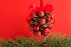 Kiefer-Kegel und rote Kugel-hängende Dekoration Stockfotografie