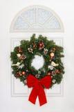 Kiefern-Weihnachtskranz mit dem roten Bogen, der an der weißen Tür hängt Stockfotos