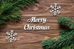 Kieferniederlassung in den Ecken des Holztischs Frohe Weihnachten Weihnachtsdekoration mit Schneeflocken Stockbilder