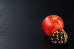 Kiefernkegel, Apfel auf schwarzem hölzernem Hintergrund Lizenzfreie Stockbilder