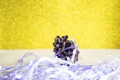 Kiefernkegel gegen das gelbe Gold des Hintergrundes und das blaue Weihnachten Stockfotos