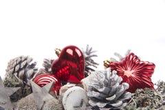 Kiefernkegel lokalisiert auf weißem Hintergrund mit Weihnachtsbällen Lizenzfreie Stockfotos