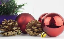 Kiefernkegel, rote Kugeln und Weihnachtsverzierung Stockfotografie