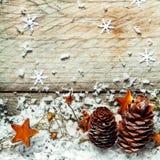 Kiefernkegel, -sterne und -schnee in einem Weihnachtshintergrund Lizenzfreies Stockbild