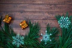 Kiefernniederlassungen und Weihnachtsdekorationen auf hölzernem Hintergrund Stockfotografie