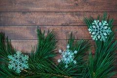 Kiefernniederlassungen und Weihnachtsdekorationen auf hölzernem Hintergrund Lizenzfreies Stockbild