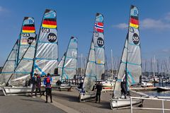 Kiel, Germany - September 9th, 2018 - Several 49er FX dinghies on the shore with their crew after training stock image