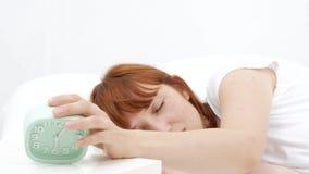 Kielzog omhoog van een in slaap meisje die wekker op het bed in de ochtend tegenhouden stock footage