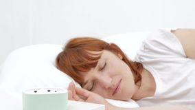 Kielzog omhoog van een in slaap meisje die wekker op het bed in de ochtend tegenhouden stock videobeelden