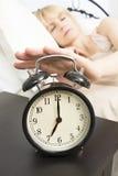 Kielzog op Tijd: Middenleeftijdsvrouw die voor Wekker bereiken Royalty-vrije Stock Afbeelding