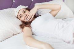 Kielzog van een het aantrekkelijke jonge donkerbruine meisjesvrouw omhoog en slokjes terwijl geeuw in haar bed in een slaapmasker stock foto's