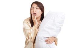Kielzog van het geeuw het Aziatische meisje omhoog slaperig en slaperig met hoofdkussen stock afbeelding