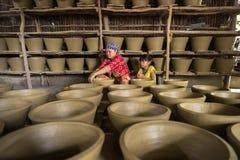 Kien Giang,越南- 2016年12月6日:做泥罐-瓦器产品的越南妇女用人工在Hon Dat区, Kien Giang PR 免版税库存照片