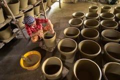 Kien Giang,越南- 2016年12月6日:做泥罐-瓦器产品的越南妇女用人工在Hon Dat区, Kien Giang PR 免版税库存图片