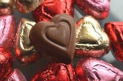 Kierowa kształta czekoladowego cukierku czerwień, menchia, złocistej folii zawijający kawałki Obrazy Stock