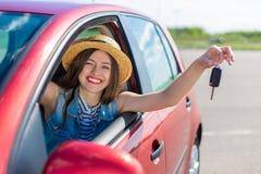 Kierowca kobieta ono uśmiecha się pokazywać nowych samochodów klucze i samochód Zdjęcie Stock